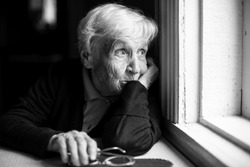 An elderly woman sadly looking out the window, a black-and-white photo.