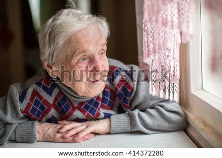 An elderly woman sits and looking out the window.