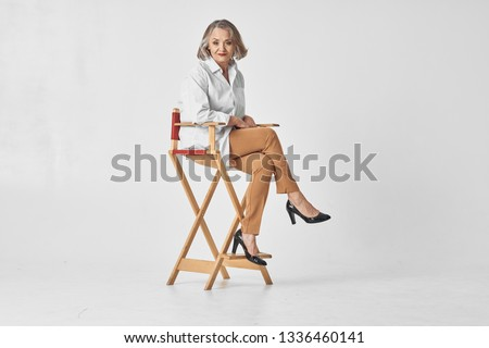 An elderly woman sits on a high chair in a white shirt Gray isolated background #1336460141