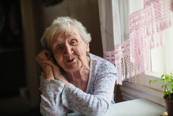 An elderly woman sitting at the table.