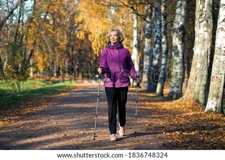 an elderly woman walks through the Park on Scandinavian sticks