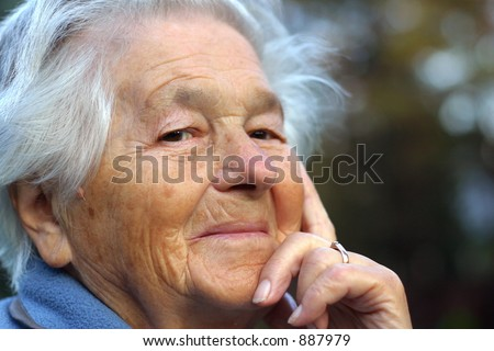 an elderly - 89 year old - woman looking into the camera and smiling. Shallow DOF.