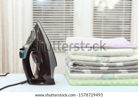 An electric black iron and a pile of ironed bed linen on the Ironing Board. #1578729493
