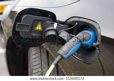 An electric car charging at a power station