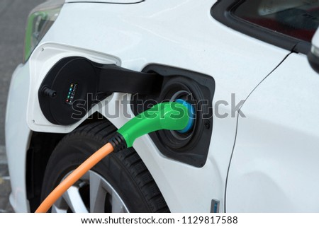 An electric car is being charged at a charging station #1129817588