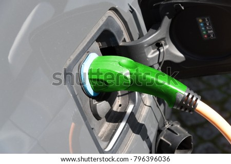 An electric car is being charged at a charging station #796396036