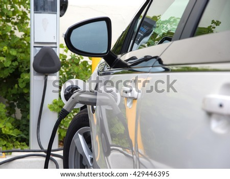 An electric car or automobile recharging at a charging station