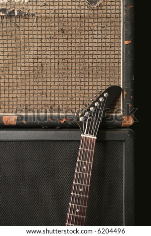 An electric guitar leaning up against an old vintage amplifier.