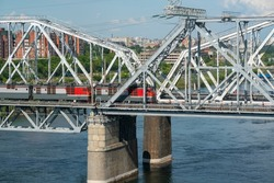 An electric train travels across a railway bridge across a river in an industrial city. Railway bridge with metal profile arches. Providing rail transport across the river.