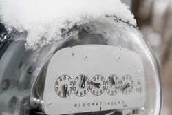 An electric utility meter with snow and ice on the top of it. Could be used to illustrate the soaring cost of utility bills during winter time.