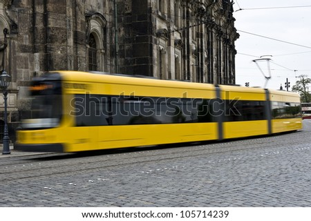 An electric, yellow trolley going in fast motion down an urban street in Dresden, Germany.