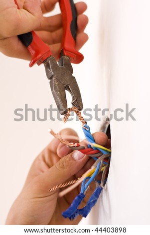 An electrician binding copper wires together and sealing them with insulation stripe.