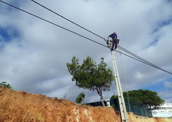 An electrician climbing an electric pole to install and repair power lines. Risky work at height.