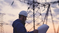 An electrician on the background of high towers of power plants looks at the project for the development of an electrical structure, the expansion of the electrical voltage of volts in the wires