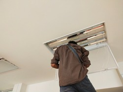 An electrician servicing the lamp on the ceiling