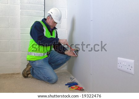 An electrician wearing safety gear installing an electrical socket