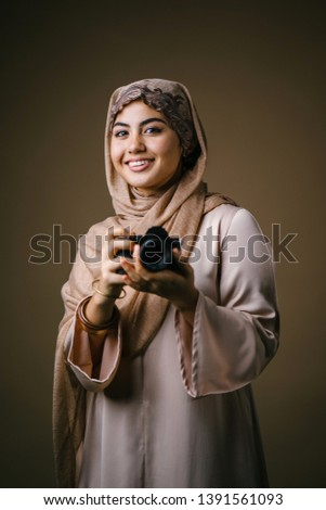 An elegant and beautiful Middle Eastern Muslim woman in a brown dress and hijab head scarf smiles as she uses her DSLR camera in a studio. She is smiling happily as she uses her camera.