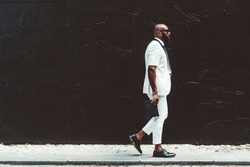 An elegant bearded bald African guy in a white fashionable short sleeve suit, sunglasses, and leather shoes, with a man's clutch in his hand, he is passing in front of a black paint wall