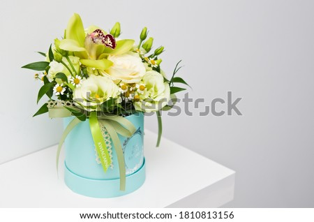 An elegant bouquet of various natural flowers in blue flower box as home decoration. Best wishes text on the box. Kwiaciarnia means Flower shop on Polish Zdjęcia stock ©