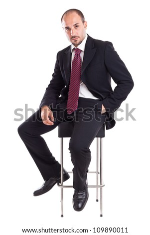an elegant businessman sitting on a footstool - stock photo