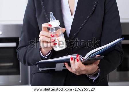 An elegant businesswoman working while holding her child's milk bottle