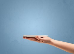 An elegant hand holding mobile phone in front of an empty clear blue wall background concept