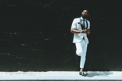 An elegant handsome bald bearded African-American guy in a fashionable white costume with a necktie and a smartphone in his hands is leaning against a black wall, with a copy space place on the left