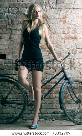 An elegant long-legged young woman with a bicycle against a brick wall.