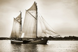 An elegant two-masted gaff schooner (tall ship) sailing near the lighthouse, close-up. Riga bay, Ba;tic sea, Latvia. History, transportation, sport, recreation, cruise, regatta. Concept image