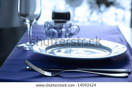 An elegant wedding table place setting in cool tones