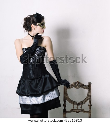 An elegant young woman in fancy dress in retro interior.