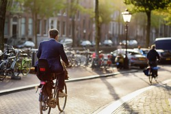 An elegantly dressed man rides a Bicycle in the center of Amsterdam. Bicycle capital of Europe.