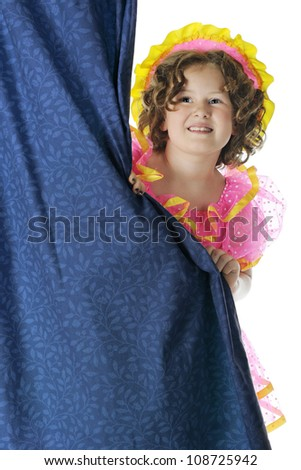 An elementary performer looking out from behind a curtain in her costume.