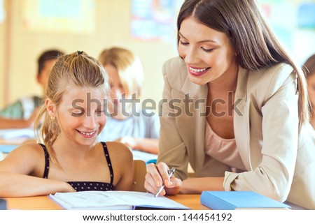 An elemetary school teacher helping one of her students.
