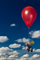 An elephant flying with a red balloon