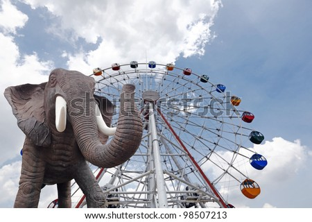 An elephant parading in front of a big colorful ferris wheel on a blue cloudy day.