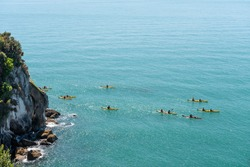 An elevated view of a group of kayakers rounding Pitt Head, Able Tasman National Park, New Zealand.