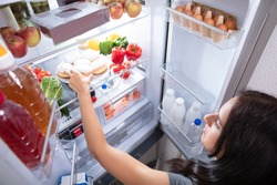 An Elevated View Of A Young Woman Taking Food To Eat From Refrigerator