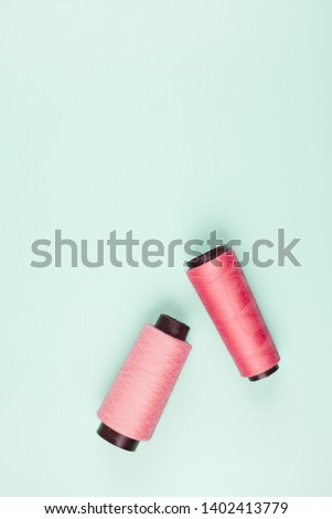 An elevated view of pink and coral spools on mint background #1402413779