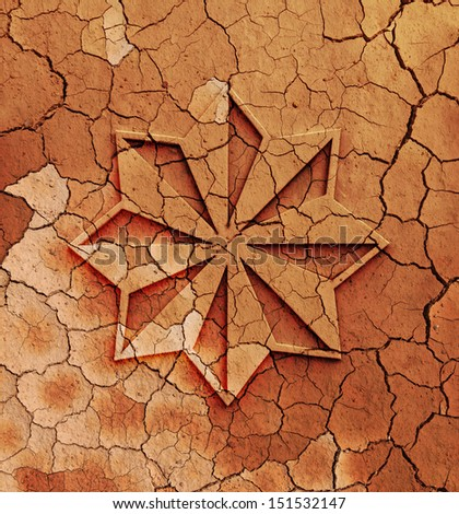 An embossed symbol of a star on the surface of a dry cracking parched red earth for the concept of celestial intervention to planet earth's climate woes.