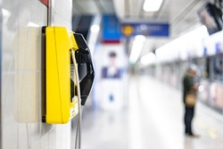 an emergency yellow land line phone cell on wall in public area of subway underground transport train station, concept of emergency calling situation on needing to contact people in urgent action