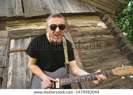 An emotional guitarist in the background plays and sings in the background of an old Russian village barn.