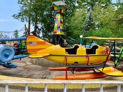 An empty amusement park ride. This spinning, thrill ride is for younger children. Each car is in the shape of an airplane and has two seats. The ride is off and not functioning.
