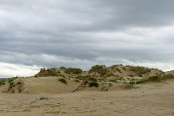 an empty beach with tall sand dunes under an overcast sky