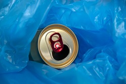 An empty beer can in a blue cellophane bag.Collection of household garbage for recycling and recycling.Copy space.