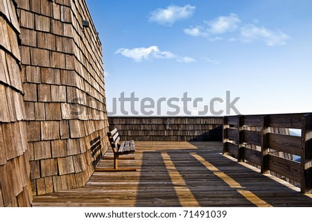 An empty bench against a wall of wood shingles on a deck.