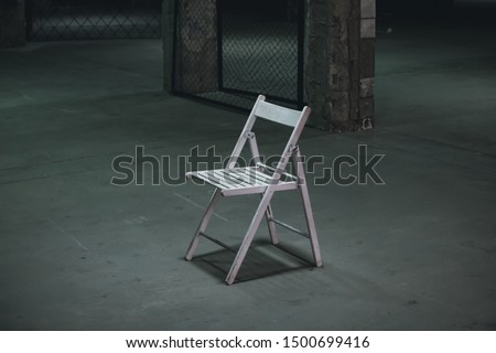 An empty chair in a dark room. A lonely object standing in empty concrete walls at dusk, a symbolism of loneliness of fear, mysticism, torture. #1500699416