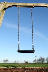 An empty child's swing in a park.
