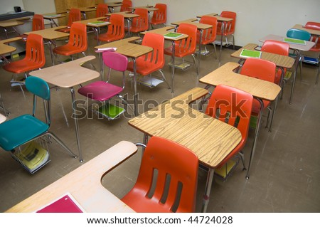 An empty class room with no students sitting in the desks. There are some notebooks laying around the room (none contain any logos.)