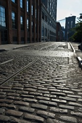An empty cobblestone street in DUMBO leads to the Brooklyn Bridge in vertical perspective